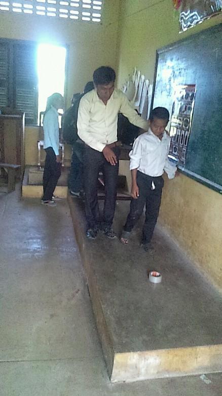 こちらの写真は現地スタッフのラブート君がガムテープを地雷に見立て、子供たちに地雷を踏んでしまったらどうなるか、というのを教えている写真です。
