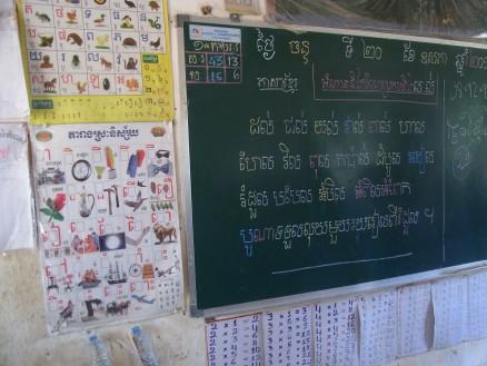黒板の左側にはカンボジア語の文字を学習するポスターが,黒板の下には掛け算の九九(9×10まである)が書かれた紙が貼られています。