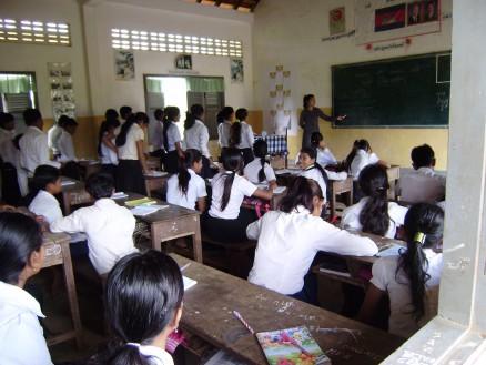 英語の授業。列ごとに生徒を立たせ,発音練習。先生「一緒に発音しましょう。ビユーティフォー」。生徒(一斉に)「ビユーティフォー」